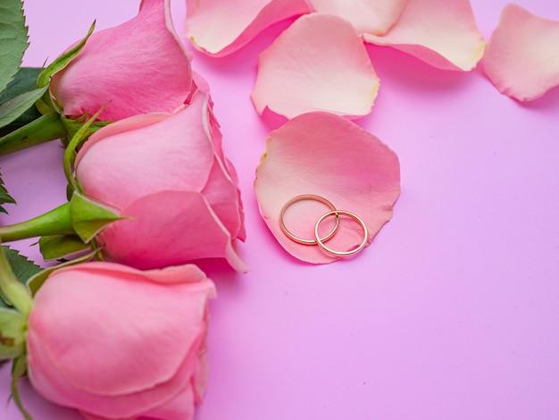 結婚式のコンセプト。 2つの結婚指輪とピンクの背景に美しいピンクのバラ。スペースをコピーします。