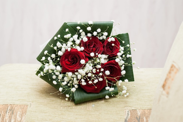 Wedding concept bouquet of red roses and wedding gold rings on light pastel background