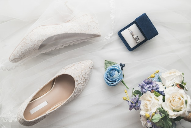 Wedding concept, bride shoes, ring and flowers