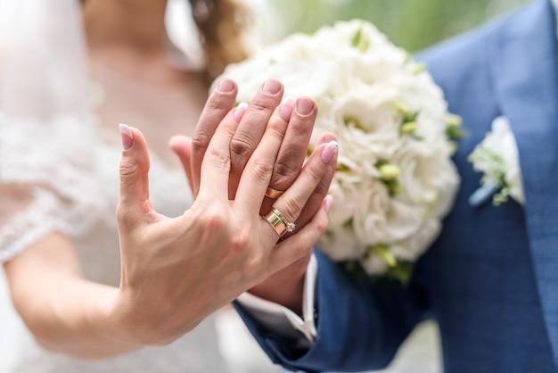 結婚式のコンセプト。花の花束に金の指輪を持つ男性と女性の手