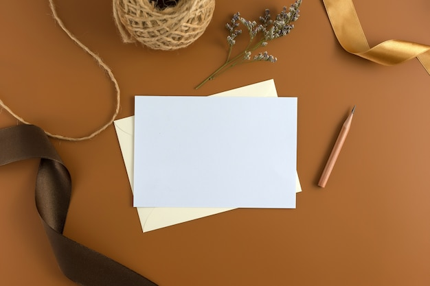 A wedding concept. wedding invitation on brown background with ribbon.