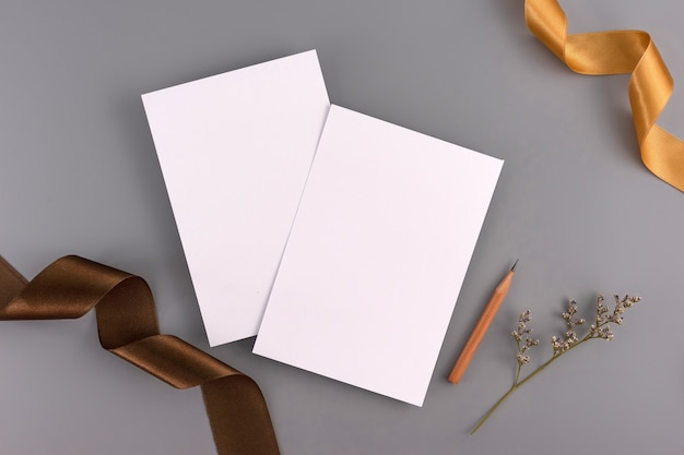A wedding concept. wedding invitation card on grey background with ribbon and decoration.