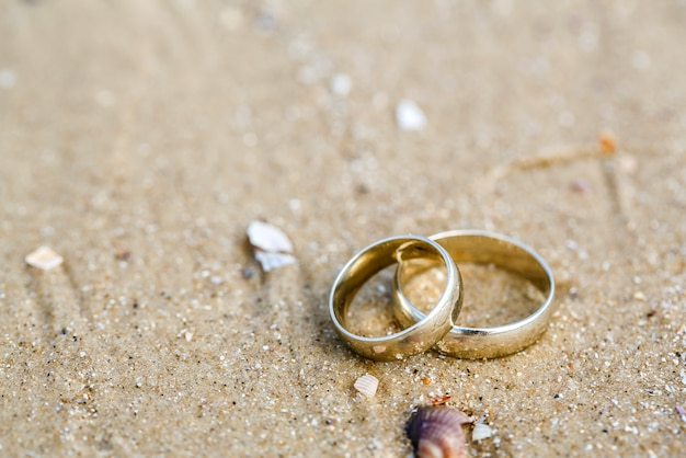 Wedding concept - wedding rings lie on sand