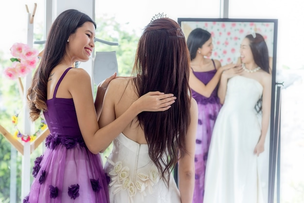Wedding concept; woman assisting bride getting dressed in wedding gown.