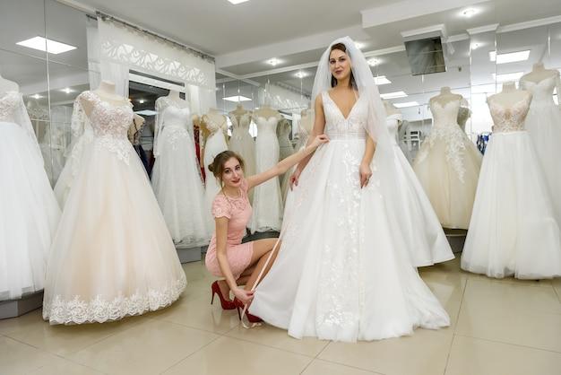 Свадебный консультант помогает невесте подобрать свадебное платье в салоне