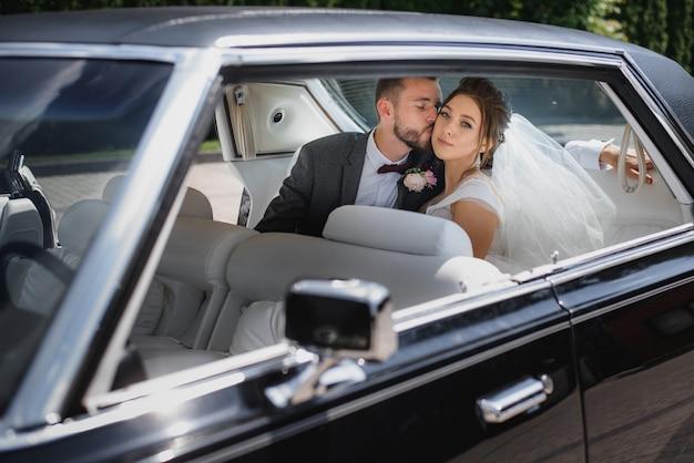 結婚式のカップルが車の後部座席に座っているとキス