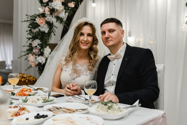 テーブルでの結婚式のカップルは休日を喜ばせます。新婚夫婦はお祭りのテーブルに座って幸せです。結婚披露宴。忠実なカップルの結婚式の日。テーブルとアーチの結婚式の装飾