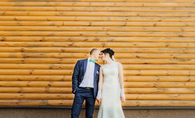 ウェディングカップル。美しい新婚者のカップルは、木製の壁にポーズ