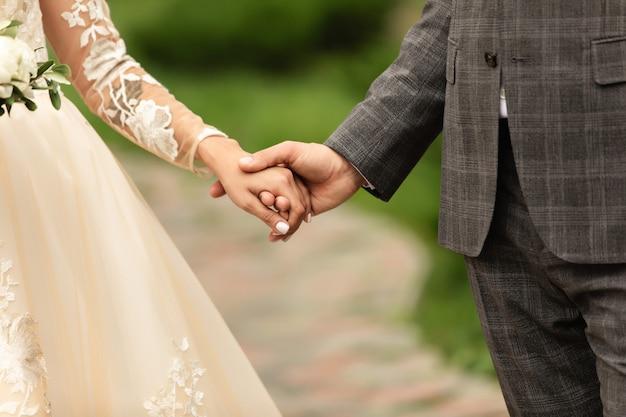 結婚式のカップル、手を繋いでいる新郎新婦、美しい結婚式の日