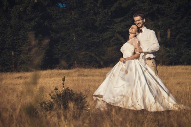 結婚式のカップル。森の中の新郎新婦、夏の時間。