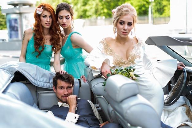 Свадебная пара жених и невеста с друзьями едут в свадебной машине