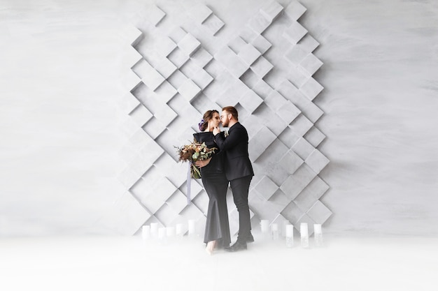 Wedding couple, bride and groom fashion portrait, over gray volumetric squares