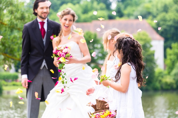 Wedding couple and bridesmaid showering flowers