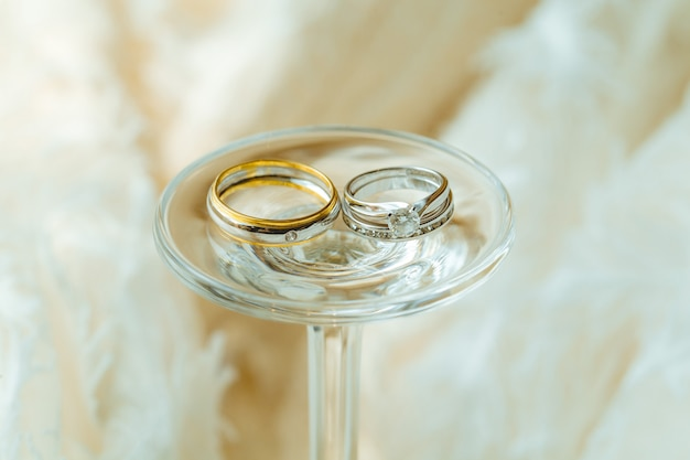Wedding couple diamond rings placed with wine glass and fabric.