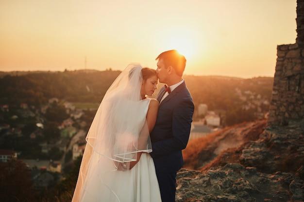 Свадебная пара, обнимая на закате. чудесная свадебная пара. прекрасная свадебная пара на закате. жених и невеста.