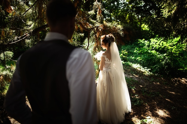 A wedding couple enjoys walking in the woods