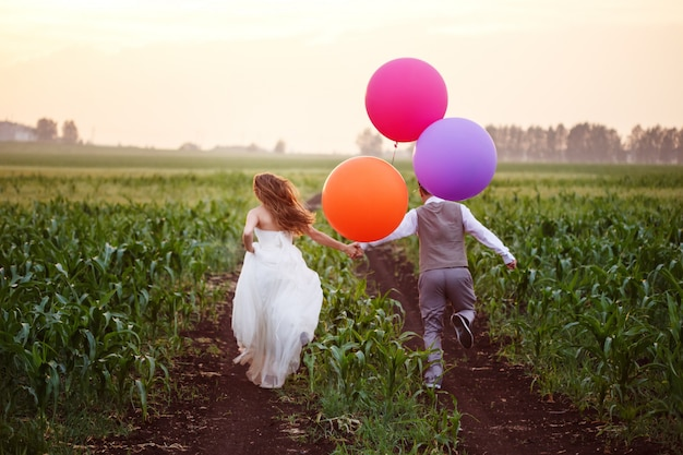 Wedding couple on the field with big balloons