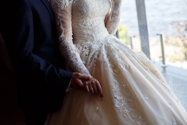 The wedding couple gently holds hands close up. man in suit and woman in lace dress gently huggings. hand in hand. wedding day. romantic moment