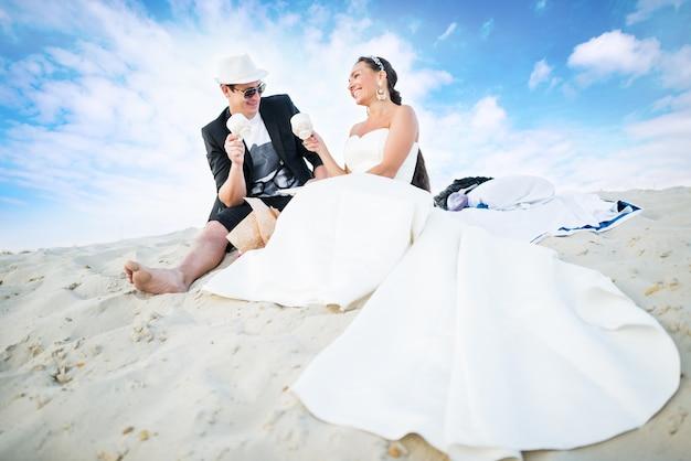 白いドレスを着た結婚式のカップルの女の子と帽子をかぶった男がビーチの白い砂の上に座っています