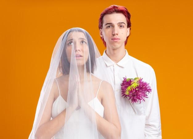 一緒にポーズをとるウェディングドレスの結婚式のカップルの新郎と新婦