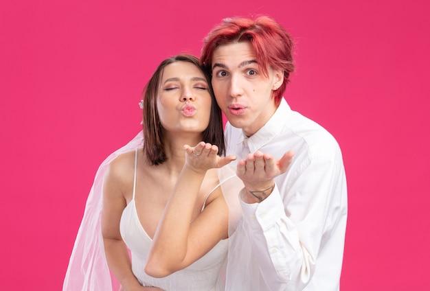 하얀 웨딩 드레스를 입은 웨딩 커플 신랑과 신부가 함께 행복한 키스를 날리며 즐겁게 웃고 있습니다.