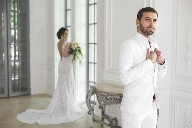 Свадебная пара жених и невеста позирует в белой студии
