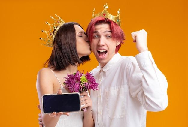 스마트폰을 들고 금 왕관을 쓰고 웨딩 드레스에 꽃다발을 든 웨딩 커플 신랑과 신부, 신랑은 행복하고 흥분한 주먹을 꽉 쥐고 있습니다.
