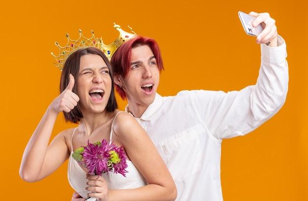 웨딩 커플 신랑과 신부는 웨딩 드레스에 꽃다발을 들고 금관을 쓰고 스마트폰으로 엄지손가락을 치켜세워 셀카를 하며 즐겁게 웃고 있습니다.