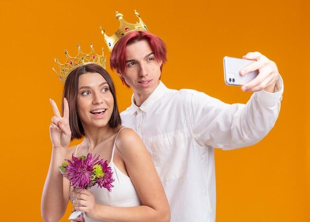 주황색 벽 위에 스마트폰을 사용하여 셀카를 하며 즐겁게 웃고 있는 금관을 쓴 웨딩드레스에 꽃다발을 든 웨딩 커플 신랑과 신부