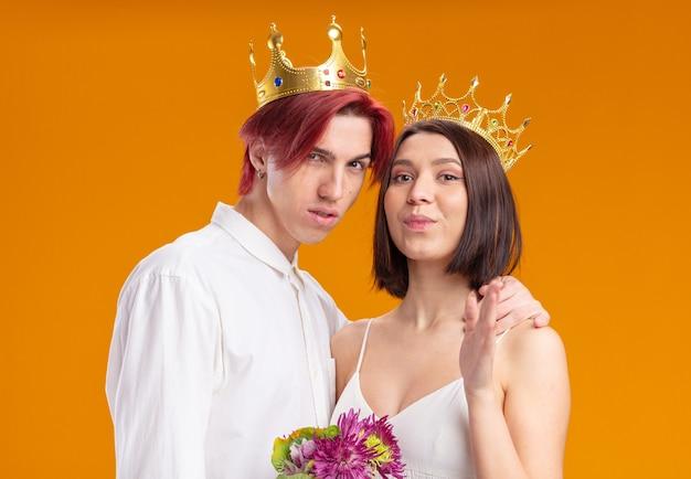 웨딩 커플 신랑과 신부가 함께 포즈를 취하면서 즐겁게 웃고 있는 금관을 쓰고 웨딩 드레스에 꽃다발을 든 신부