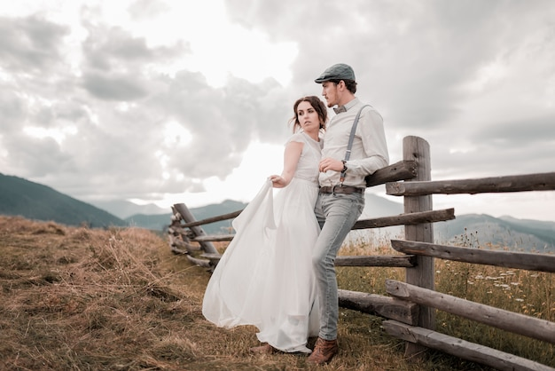 Wedding couple, groom and bride near wedding arch on a background mountain river