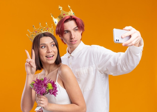 Sposi sposo e sposa con un mazzo di fiori in abito da sposa che indossa corone d'oro sorridendo allegramente facendo selfie utilizzando smartphone in piedi sul muro arancione