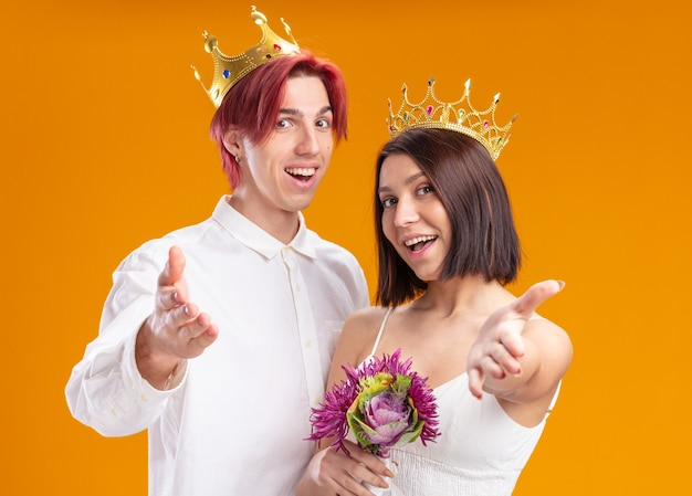 Wedding couple groom and bride with bouquet of flowers in wedding dress wearing gold crowns smiling cheerfully making come here gesture with hands