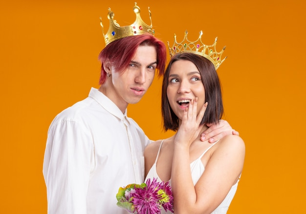 Wedding couple groom and bride with bouquet of flowers in wedding dress wearing gold crowns smiling cheerfully posing together