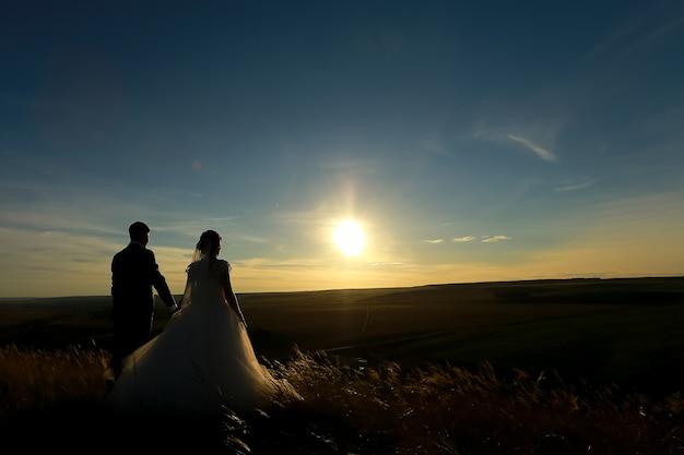 結婚式のカップルは夕日に手をつないでください。花嫁と花婿のシルエット。コピースペース