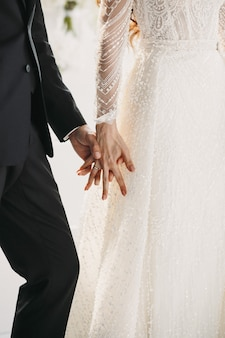 Wedding couple hold hands