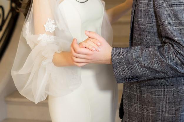 手をつないで結婚式のカップル。新郎新婦