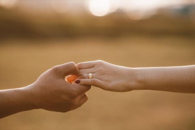結婚のために手をつないでいる結婚式のカップル