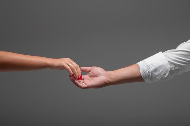 손을 잡고 웨딩 커플입니다. 회색 배경에 신랑과 신부