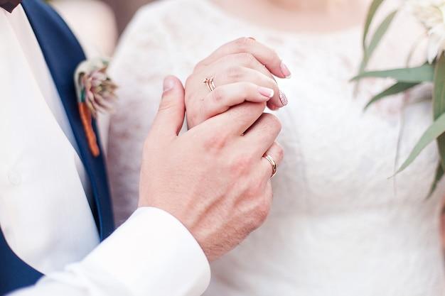 ウェディングカップルは手を握っている