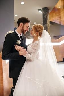 一緒に人生の最初の日、抱き合ったりキスしたりする結婚式のカップル。結婚式の後の新郎新婦、美しいカップルはお互いを愛し、抱き合っています