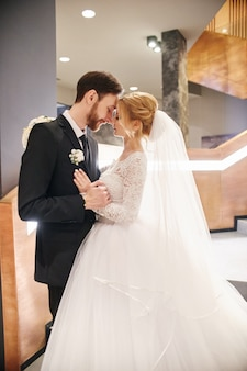 抱き合ったりキスしたりする結婚式のカップル