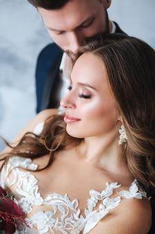 結婚式のカップルが屋内でお互いをハグします。除草カップルのクローズアップの肖像画。新郎と美の花嫁。
