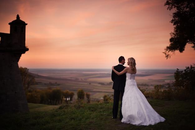Свадебная пара обнимается на фоне заката гор