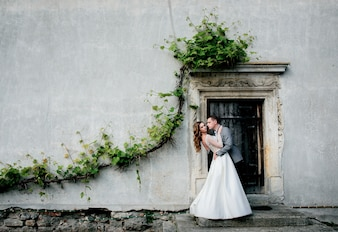 Wedding couple hugs before a wall with greenery