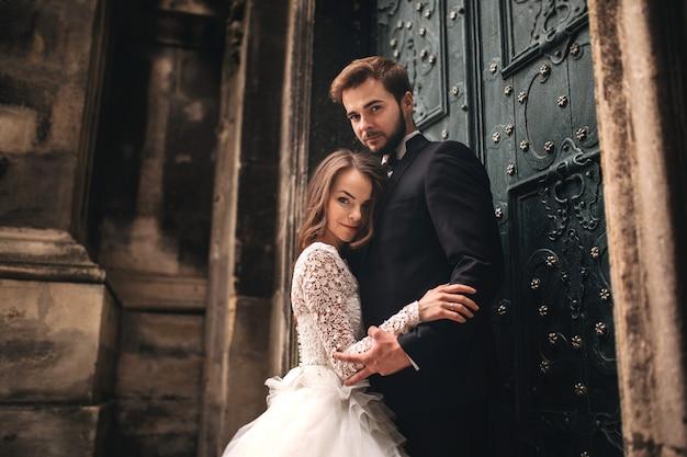 Свадебная пара обнимается возле старинной зеленой двери. каменные стены на фоне древнего города. невеста с длинными волосами в кружевном платье и жених в костюме и галстуке-бабочке. нежные объятия. романтическая любовь.
