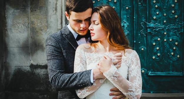 結婚式のカップルは、ヴィンテージの緑のドアの近くで抱擁します。古代の町の背景の石の壁。レースのドレスとグレーのスーツと蝶ネクタイの新郎の髪を下にした素朴な花嫁。優しい抱擁。ロマンチックな恋。