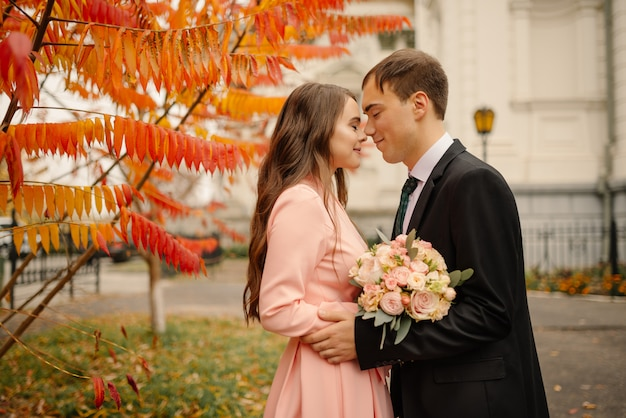 Wedding couple hugs in the old city at autumn. stone walls of ancient church. romantic love in vintage atmosphere street. gothic cathedral.