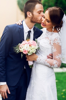 Свадебная пара в любви, целоваться и улыбаться. молодая довольно элегантная невеста и ее красивый жених, позирует в зеленом парке.