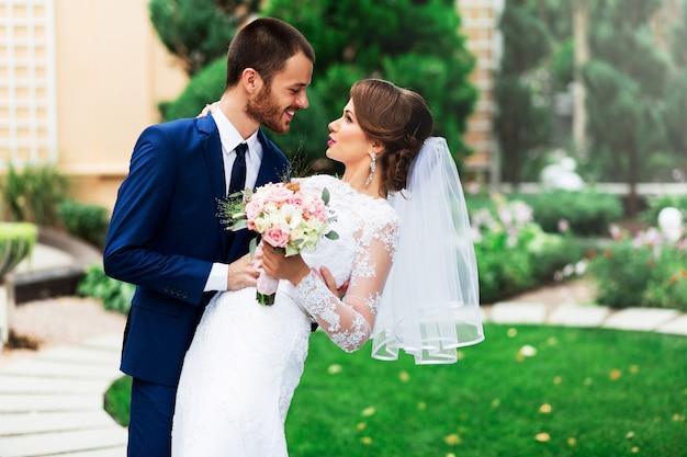 愛のキスと笑顔の結婚式のカップル。若いかなりエレガントな花嫁と緑豊かな公園でポーズをとる彼女のハンサムな新郎。
